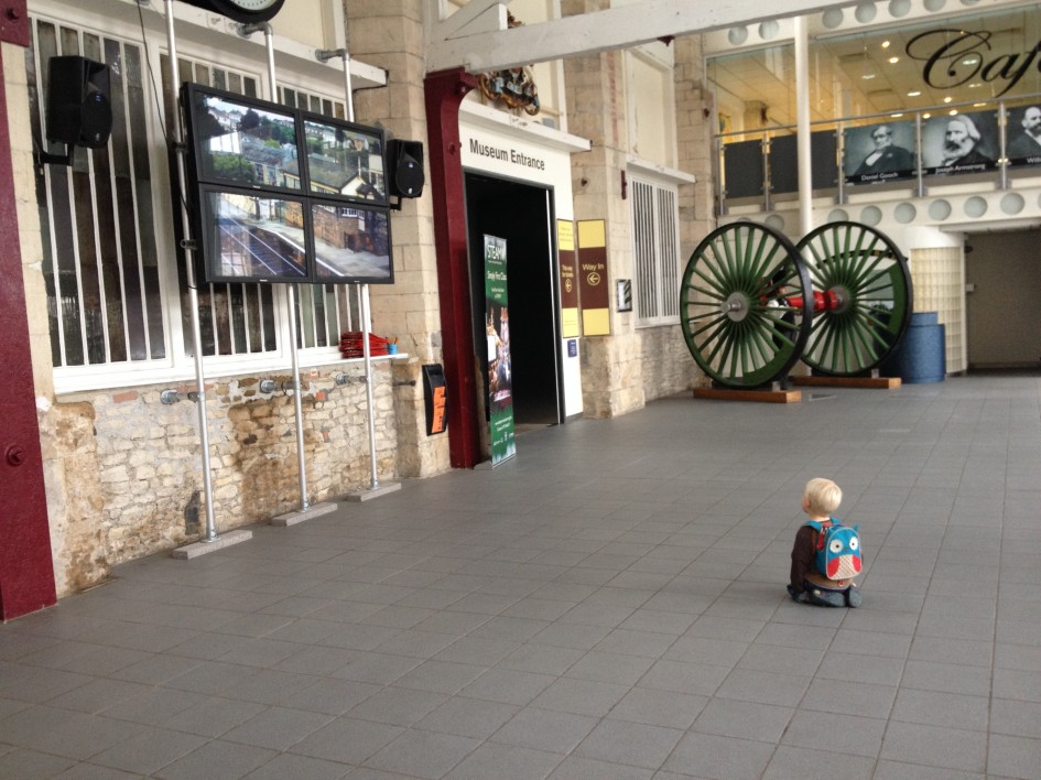 Photo of our son kneeling on the floor at the entrance of the Steam railway museum